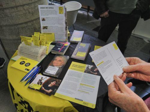 Tisch mit Infomaterialien zum Weltfrauentag 2020. Zwei Hände halten eine Aktionspostkarte zum Fall von Nasrin Sotoudeh.