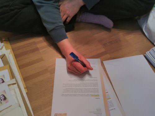 Jemand unterschreibt Briefe vom Amnesty-Briefmarathon